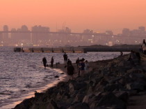 With downtown San Diego in the background, families gather at Chula Vista Marine Park to watch the sky change color after the sun sets